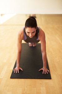 Fit woman doing press ups in a gym