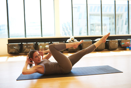 Woman Practicing Pilates on Floor Mat in Studio