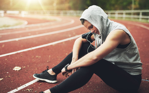 Young woman sitting on track field and preparing before running