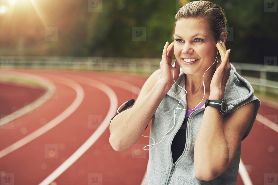 Smiling young woman listening to music while standing on stadium