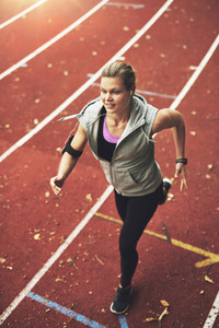Athletic young woman running on track field