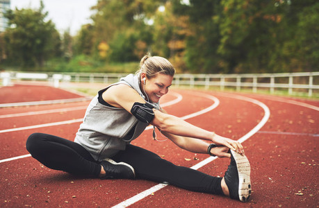 Smiling young female athlete stretching while sitting on stadium