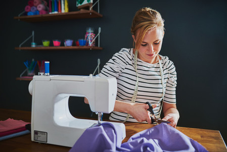 Creative woman cutting fabric