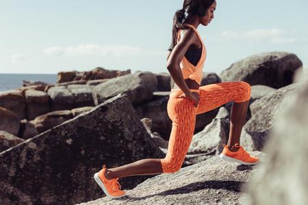 Female runner stretching legs on rocks