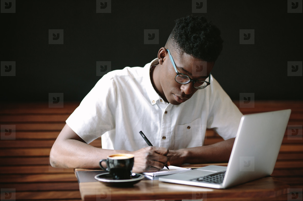 Freelancer working on laptop computer at coffee shop