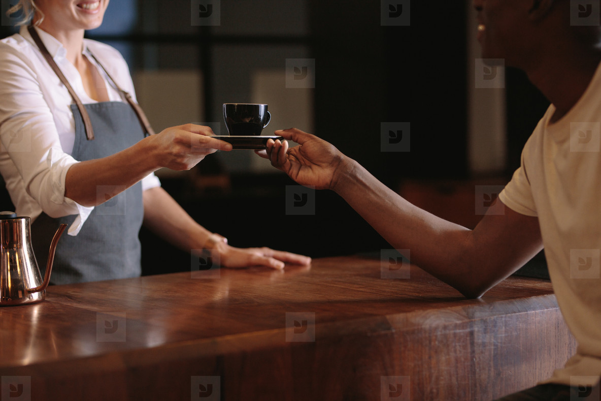 Female barista serving customer inside a coffee shop