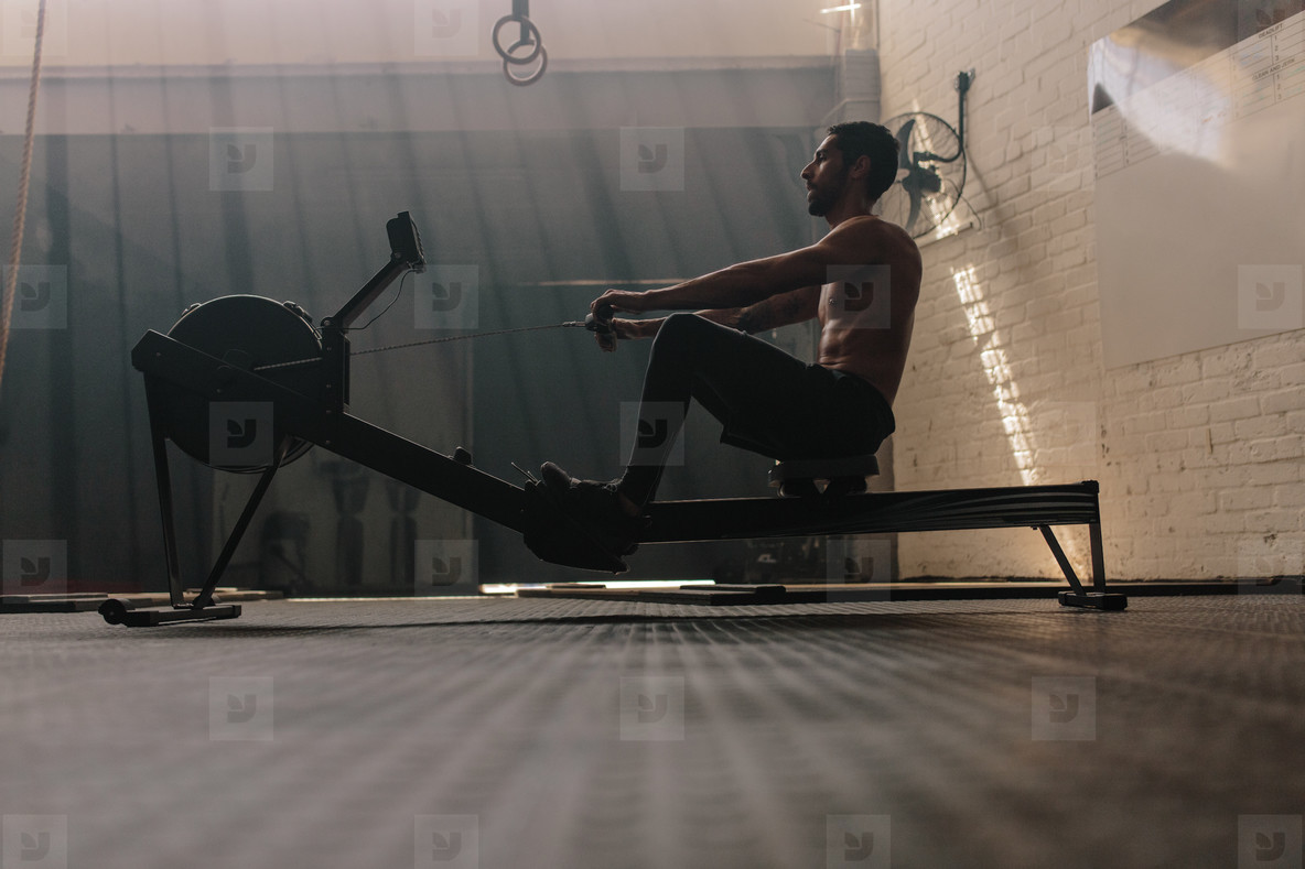 Male using rowing machine at fitness club