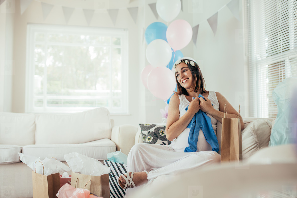 Smiling woman with new gifts at baby shower party