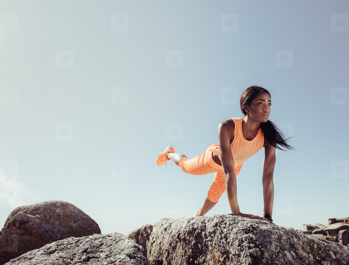 Female doing stretching exercises on beach rocks
