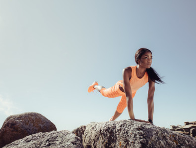 Female doing stretching exercises on beach rocks