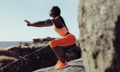Healthy woman stretching at seaside rocks