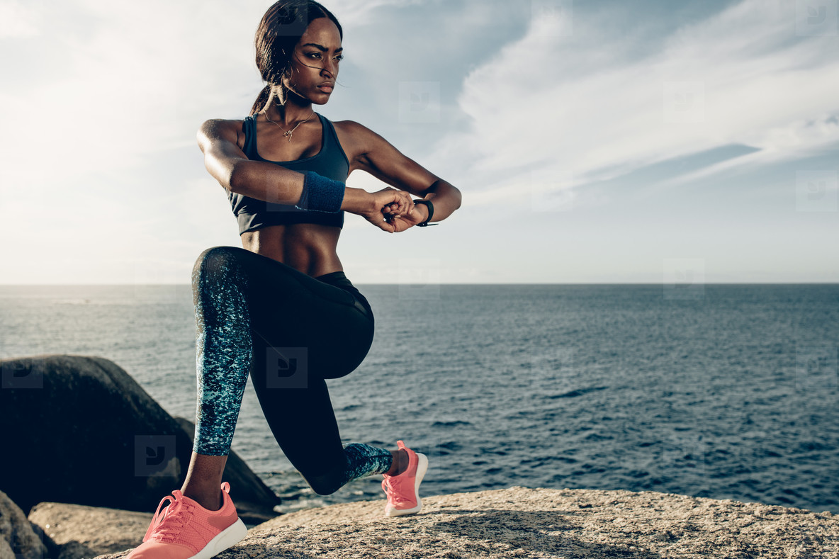 Woman doing stretching exercises by the beach