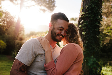 Handsome young man embracing his girlfriend in a park
