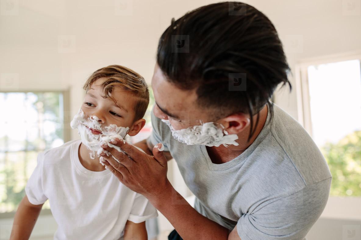Man applying shaving foam in his sons face