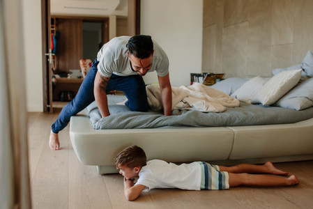 Father and son playing hide and seek in bedroom