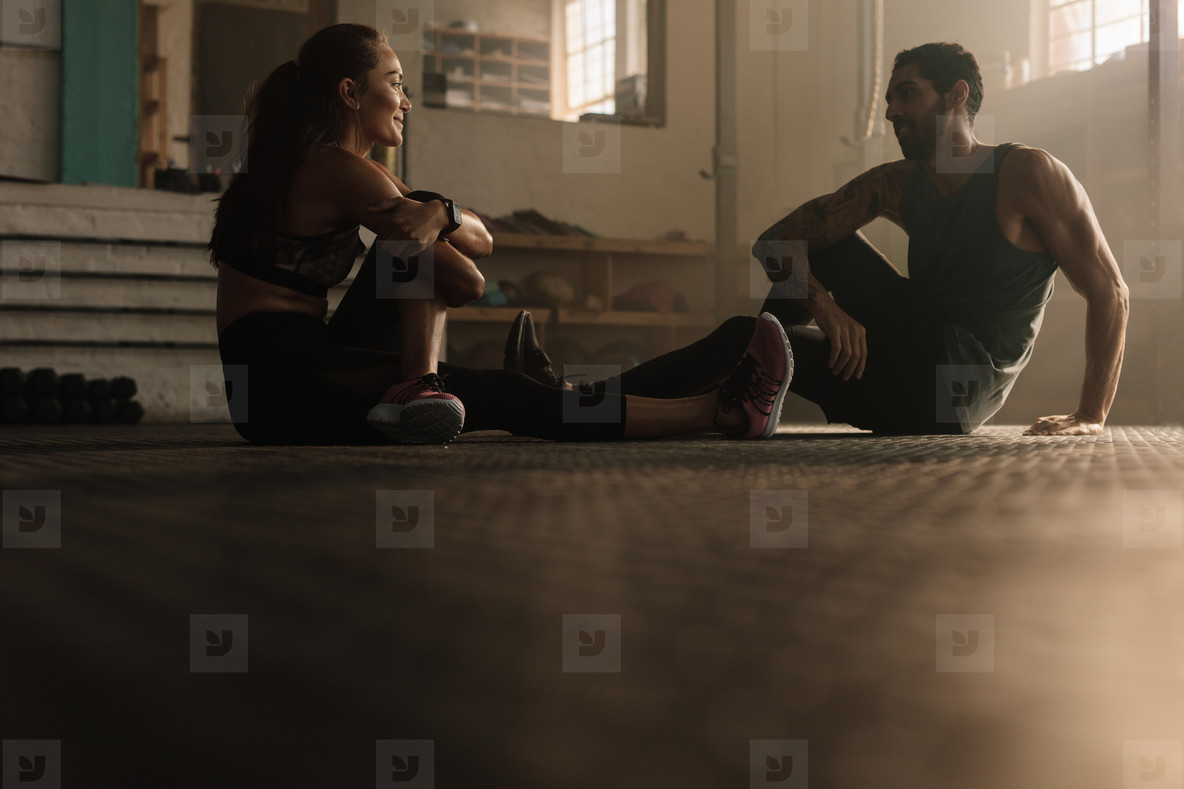 Couple taking break after training session at gym