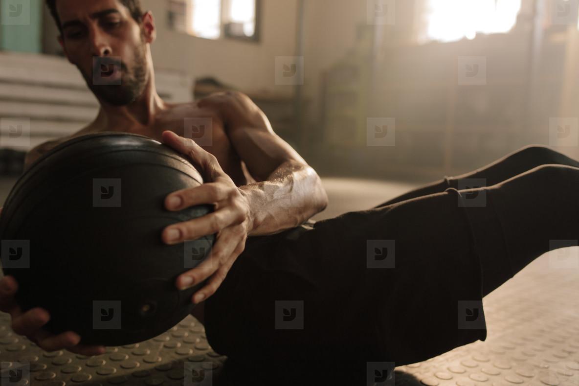 Man doing abdominal ball exercise at gym