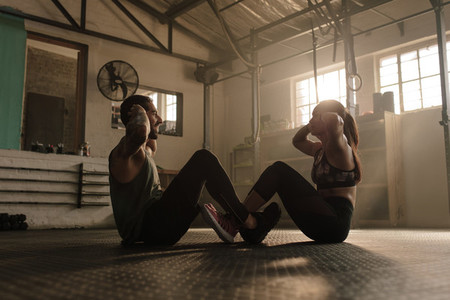 Fitness couple doing abs workout in gym