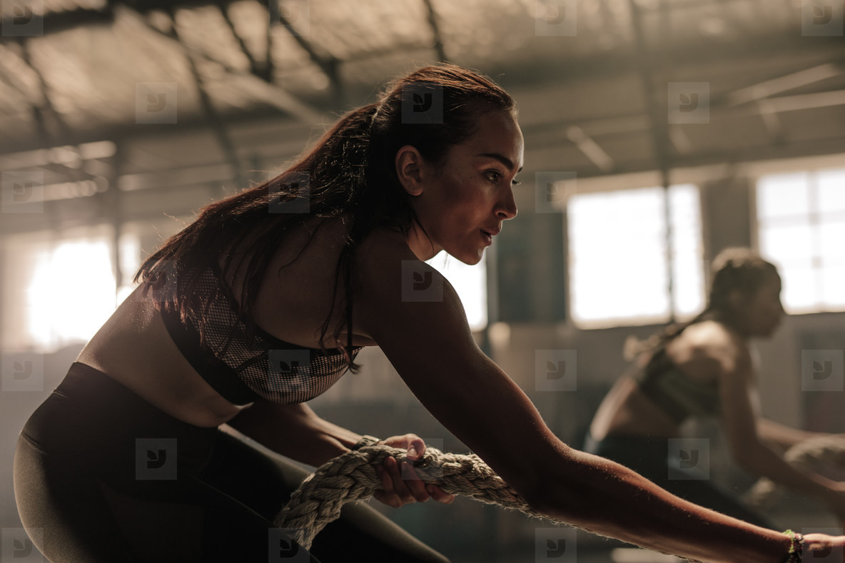 Fitness females pulling heavy rope at gym
