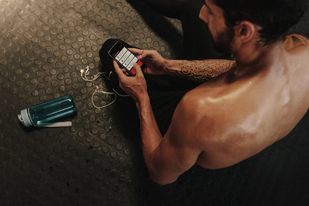 Man using fitness app on phone during break