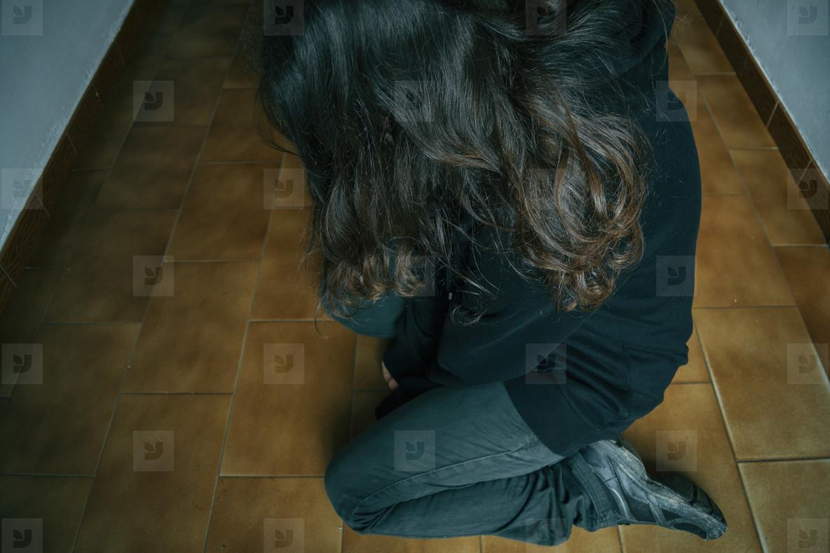 sad girl kneeling on the floor