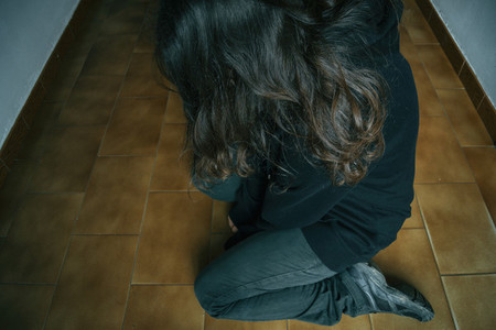 sad girl kneeling on the floor