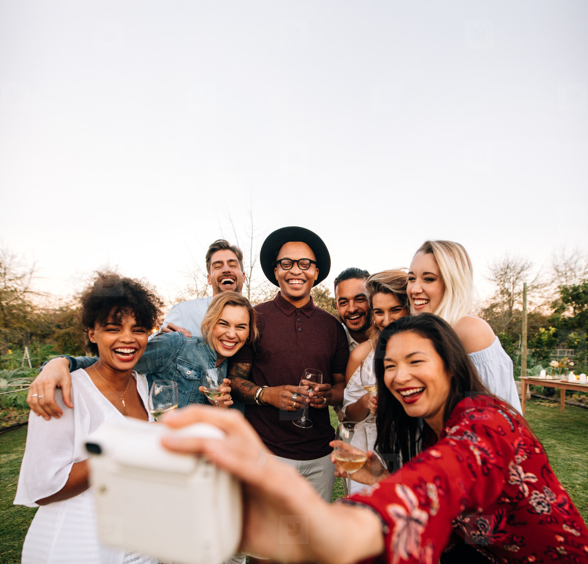 Group of friends taking picture with instant camera