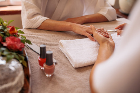 Manicurist shaping female clients nails at beauty salon