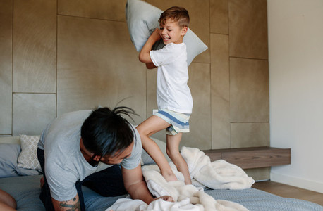Father and son enjoying playing pillow fight in bedroom