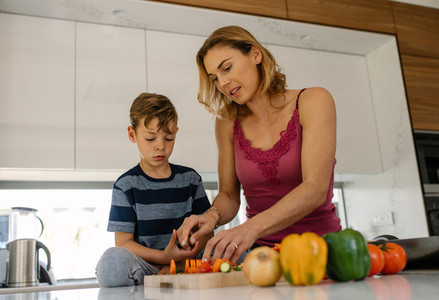Mother and son cooking together in kitchen