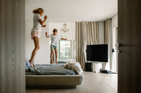 Mother and son jumping on bed