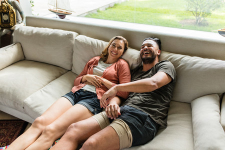 Smiling young couple relaxing on sofa