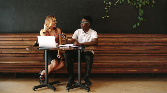 Man and woman entrepreneurs discussing work at a coffee shop