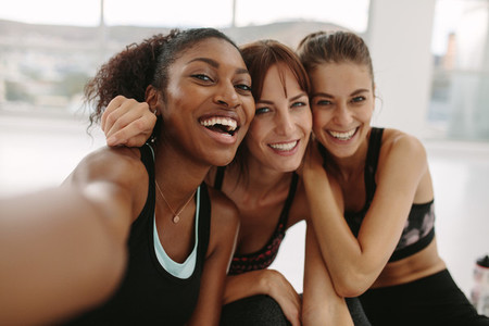 Smiling women friends taking selfie in fitness studio