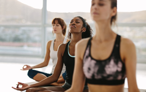 Women meditating in lotus pose at yoga class