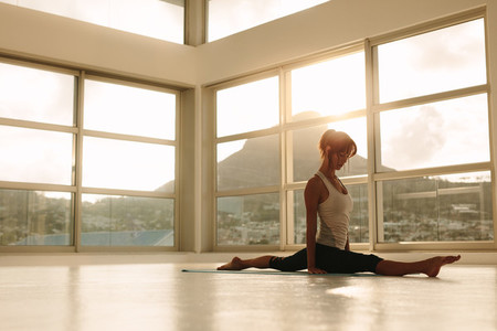 Woman practicing yoga leg split pose