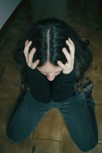 sad girl kneeling on the floor with hands on her head