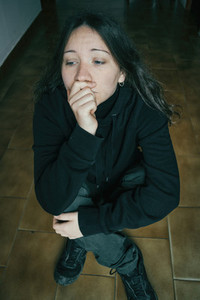 Thoughtful girl sitting on the floor with one hand in her mouth