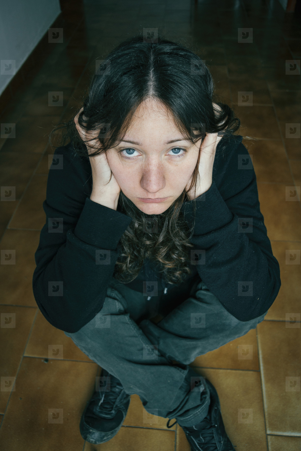 thoughtful girl sitting on the floor with her hands on her head