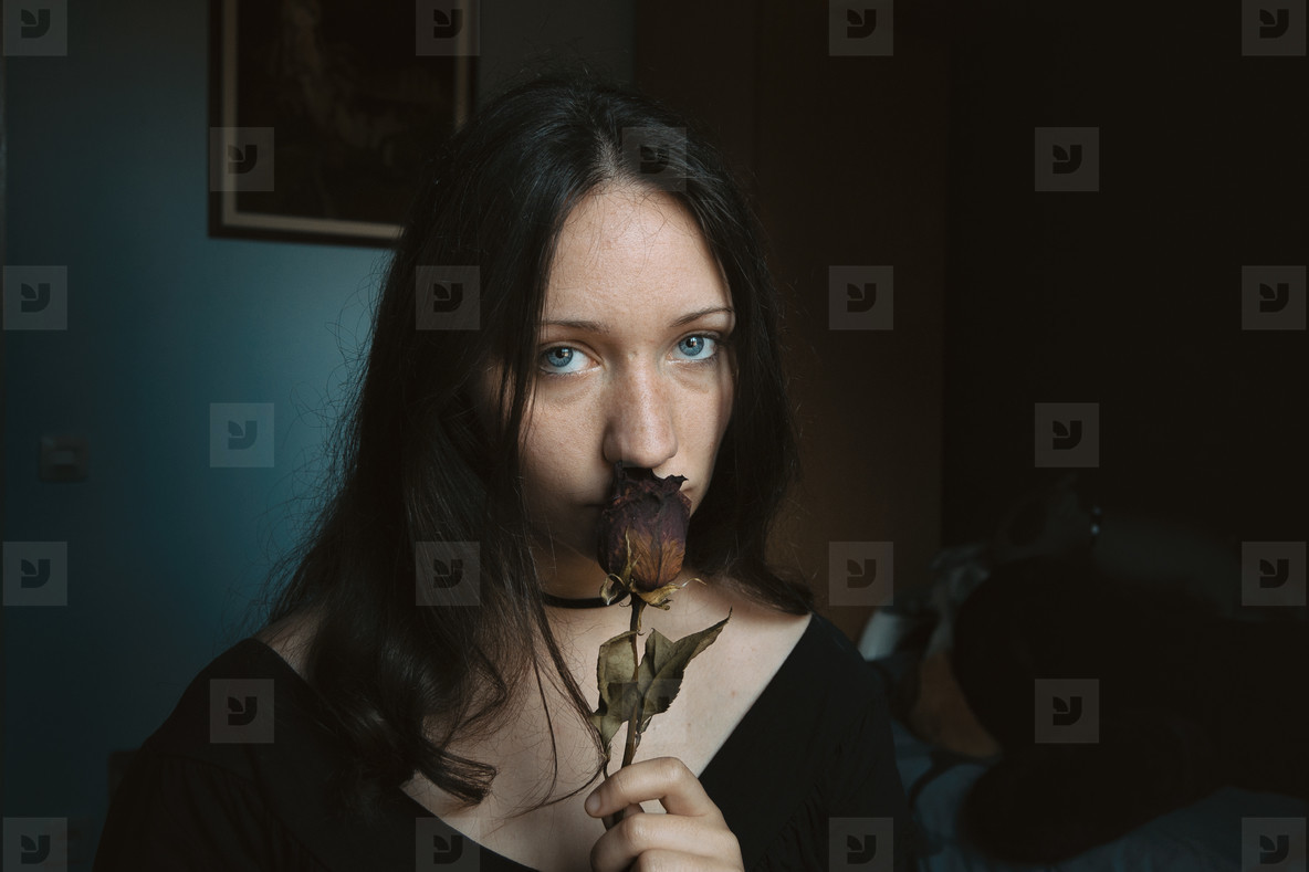 girl looking at camera with a dry rose