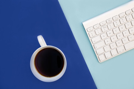 Coffee cup and computer keyboard on minimal bright blue backgrou