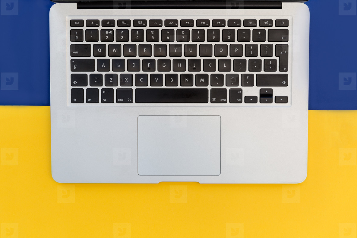 Laptop computer keyboard on minimal bright yellow and blue backg