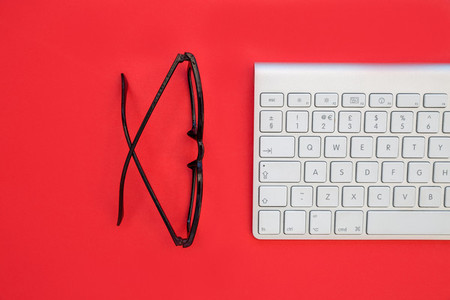 Wireless computer keyboard and eyeglasses on bright red backgrou