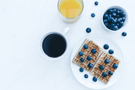 Waffles and blueberries breakfast with coffee and orange juice