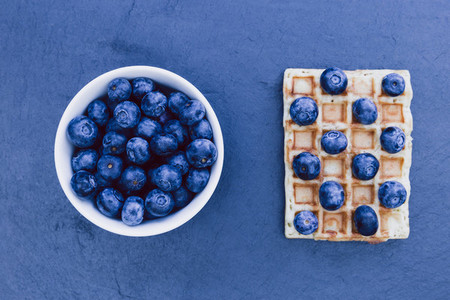 Waffles and white bowl of blueberries for breakfast on dark back