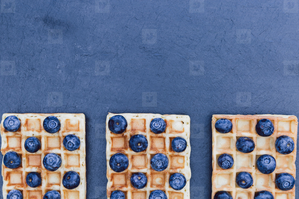 Waffles and blueberry breakfast on dark background with copy spa