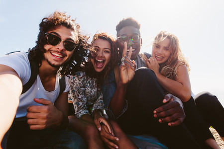 Excited friends taking selfie outdoors
