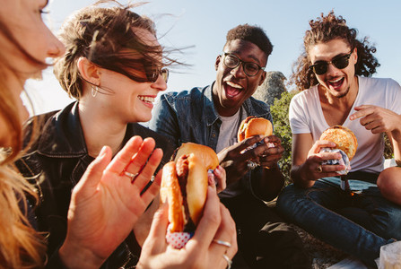 Group of friends eating burger on mountain top