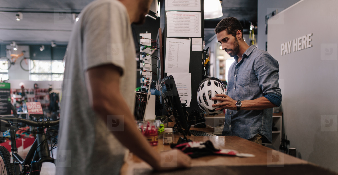 Shop owner selling helmet to customer