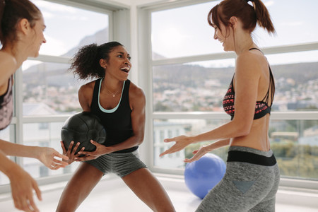 Women enjoying exercising with medicine ball at gym